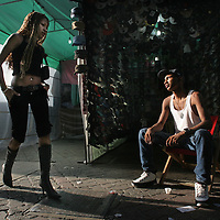 "Eduard, 20, who lives and works in a tent in the Sabana Grande neighborhood of Caracas, passes time watching a young woman walk by, Friday, December 15, 2006.  Buhoneros, thousands of workers who sell products from clothing and accessories to household goods and bootleg DVDs, make up the controversial ""informal economy.""  While many Caracas residents complain that the buhoneros have taken over streets with their makeshift marketplace, many buhoneros give thanks to Venezuelan President Hugo Chavez for allowing them a way to survive by creating their own small businesses."