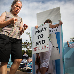 | Weston Kenney | westonkenney@archstl.org | Instagram: westonkenney <br /> <br /> Protesters stood outside Planned Parenthood facility on Forest Park Blvd. in St. Louis in response to a video that surfaced that showed a Planned Parenthood worker negotiating selling fetal tissue from abortions. Mary Roy, one of the many protesters that stood outside Planned Parenthood, walked the perimeter of the facility while praying the rosary on Tuesday, July 21, 2015.