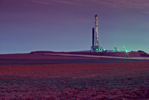 Stock photo of on-shore oil and gas drilling rig behind a field of native vegetation in Oklahoma.