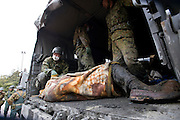 Members of Japan's Self Defense Forces lift onto a guerny the corpse of a man killed during the March 11 earthquake and tsunami in Ishinomaki, Japan on 15 March, 2011.  Photographer: Robert Gilhooly