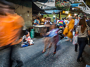 04 JANUARY 2016 - BANGKOK, THAILAND:        Morning commuters walk past a beggar in the entrance to Bang Chak Market on the last day the market was open. The market closed January 4, 2016. The Bang Chak Market serves the community around Sois 91-97 on Sukhumvit Road in the Bangkok suburbs. About half of the market has been torn down. Bangkok city authorities put up notices in late November that the market would be closed by January 1, 2016 and redevelopment would start shortly after that. Market vendors said condominiums are being built on the land.      PHOTO BY JACK KURTZ