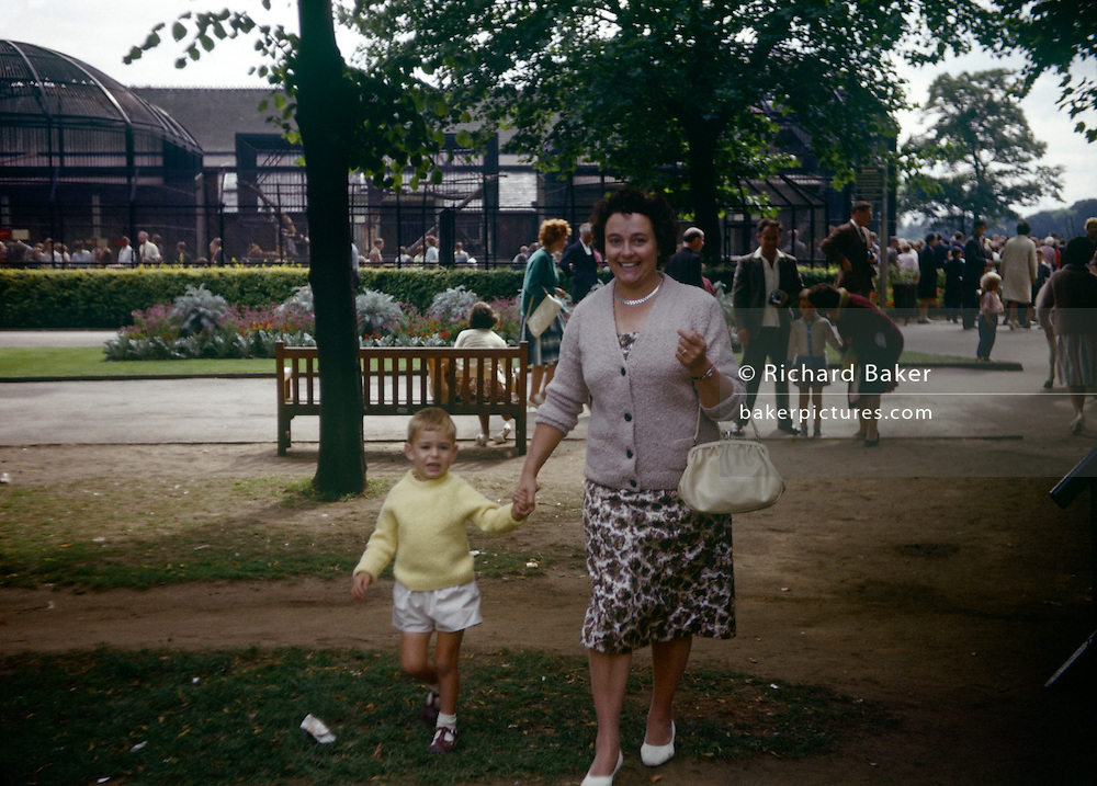 A mother holds the hand of her 5 year-old son during a visit to London zoo in the early 1960s. Looking frightened and upset, the small lad walks hand in hand with his mum, away from where there are scary wild animals in cages but still a frightening experience to a little person. The mother is smartly-dresed for the family day out to the capital and its zoo in Regents Park. It was was recorded on film camera by the boy's father, an amateur photographer in 1962. The picture shows us a memory of nostalgia in an era from the last century.