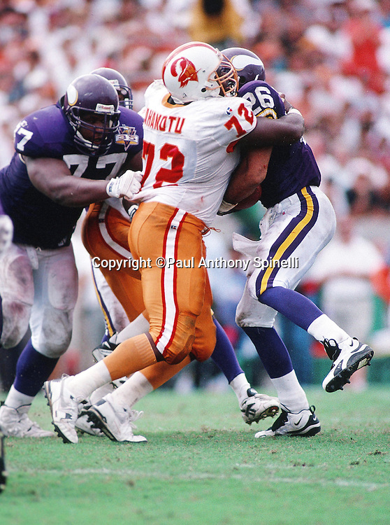 Minnesota Vikings running back Robert Smith (32) gets tackled by Tampa Bay Buccaneers defensive end Chidi Ahanotu (72) during the NFL football game against the Tampa Bay Buccaneers on Oct. 15, 1995 in Tampa, Fla. The Bucs won the game 20-17 in overtime. (©Paul Anthony Spinelli)