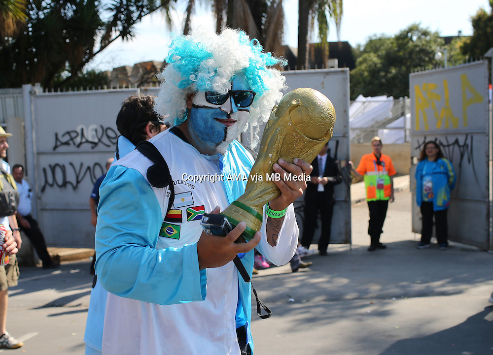 A fan of Argentina holding a replica of the FIFA World Cup Trophy