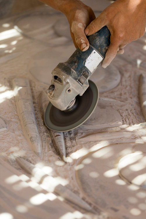 Workers create table top surfaces and ornaments with natural rock fossil patterns using stone found in the Erg Chebbi and Foum Zguid region of the Moroccan Sahara desert, Erfoud Fossils, Southern Morocco, 2015-06-09.