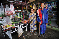 Ibu Aban Daeng with her husband, Bapak Emba Daeng, outside their vegetable shop at the Jongaya leprosy settlement, Makassar, Sulawesi, Indonesia. Ibu Aban Daeng, 63, is originally from Gowa, Sulawesi.  Her husband, Bapak Emba Daeng, is from Bone, Sulawesi.  Both were infected with leprosy at an early age.  They met in Jongaya and married in 1967, 7 years after Ibu Aban moved to the settlement.  For the last 10 years she has run a vegetable kiosk in Jongaya and recently bought a cart using money loaned from Permata.  Her husband now sells vegetables from the cart around the settlement.