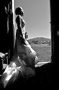 Bride looking out from a barn door on her wedding day.