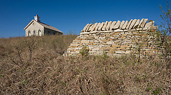 Lower Fox Creek School is a one-room schoolhouse located in the Tallgrass Prairie National Preserve. Also pictured is a portion of a restored stone wall fence. The schoolhouse had been completed in 1882 with the first school semester beginning on September 1, 1884. Average enrollment was between 1-19 students that included all grades. The school was closed in 1930. In 1968 the Garden Clubs in the Mid-East District of Kansas renovated the building. The school is on the National Register of Historic Places. Tallgrass Prairie National Preserve is the only unit of the National Park Service dedicated to the preservation of the tallgrass prairie ecosystem. The Tallgrass Prairie National Preserve is co-managed with The Nature Conservancy. The 10,894-acre preserve is located in the Flint Hills of Kansas in Chase County near the towns of Strong City and Cottonwood Falls.