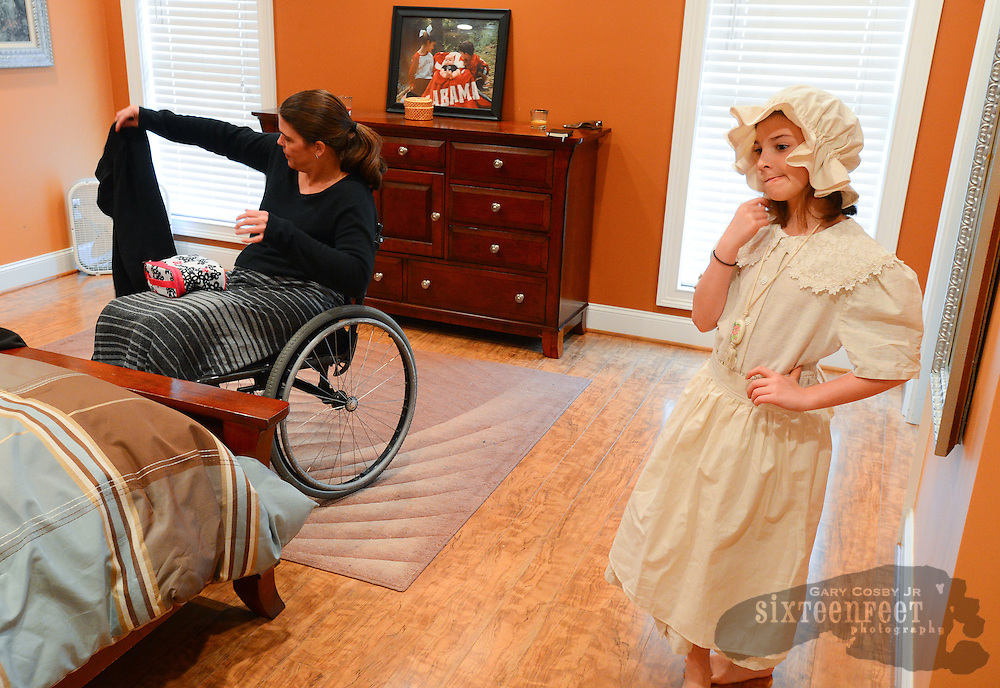 Gary Cosby Jr./Decatur Daily    Courtney Carpenter Boyll was a rising star athlete in 1994 when a car wreck left her paralyzed.   Twenty years later she is a wife, mother of three and third grade teacher and does it all as a paraplegic.  Courtney picks up clothes from the bedroom floor while Ava thinks about what her role in the school play will be like later in the evening.