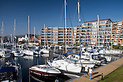 People passing yachts and power boats moored at Port Solent marina, near Portsmouth, South Coast of England, UK