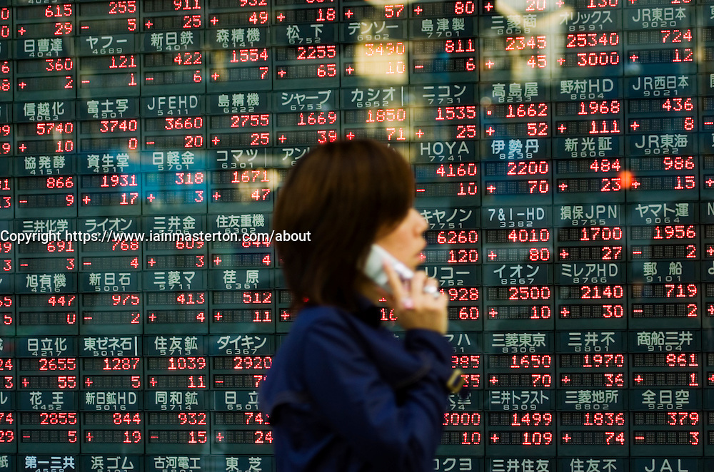 Woman walks past electronic diplay board showing stock market prices of companies in central Tokyo Japan