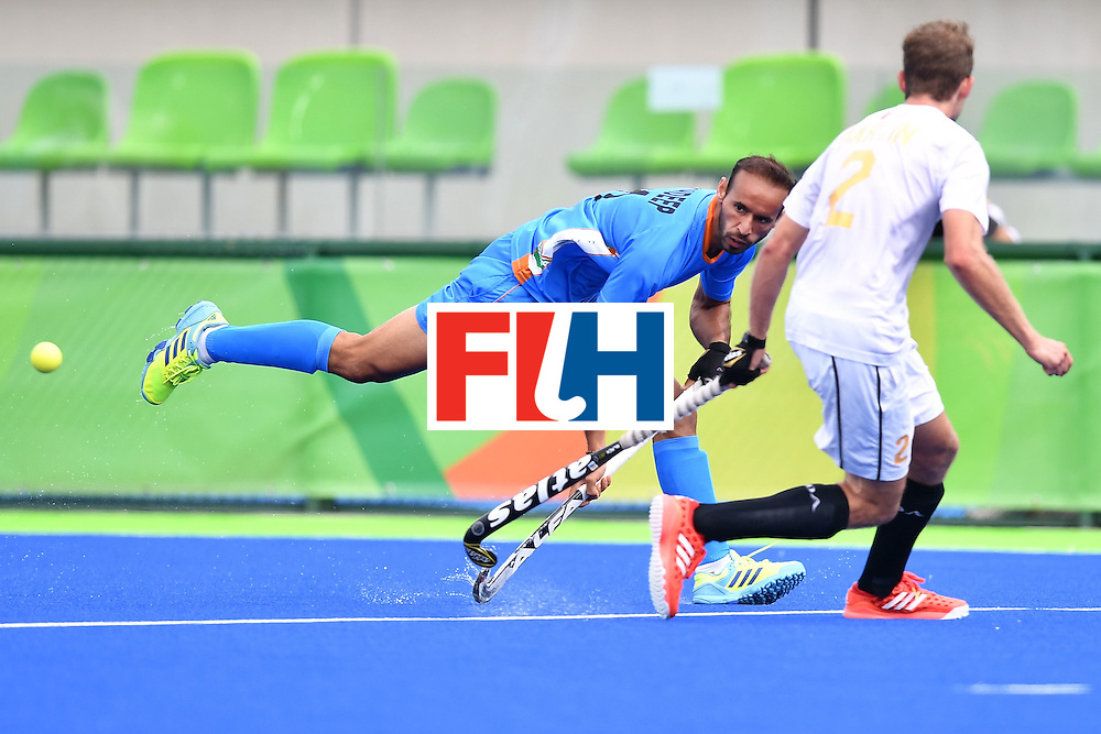 India's Ramandeep Singh (L) shoots past Canada's Benjamin Martin during the mens's field hockey India vs Canada match of the Rio 2016 Olympics Games at the Olympic Hockey Centre in Rio de Janeiro on August, 12 2016. / AFP / MANAN VATSYAYANA        (Photo credit should read MANAN VATSYAYANA/AFP/Getty Images)