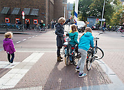 In Utrecht zet een vrouw met twee dochters de fietsen neer bij een paal.<br /> <br /> In Utrecht a woman with two daughters is parking their bicycles.