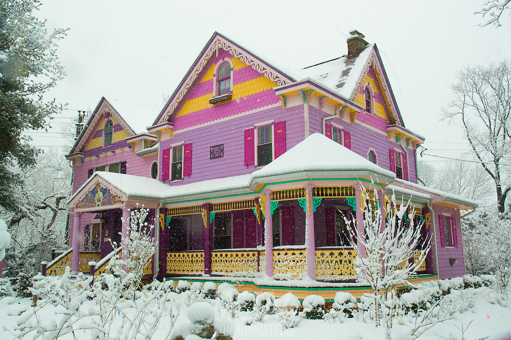 A colorful home stands in stark contrast to the white snow all around.