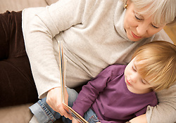 Grandmother lying on floor with toddler reading