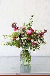 Arrangement of spring flowers in a large glass jam jar