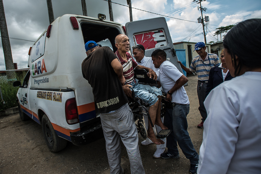"""BARQUISIMETO, VENEZUELA - JULY 29, 2016: Dementia patient Mario López is loaded onto an ambulance while he was choking on a piece of food that his daughter, Mayori López, had brought him during a visit.  When nurses couldn't dislodge the food, they called for a doctor, but there was no doctor present.  They they called for an oxygen tank…but there was no oxygen in the hospital either.  They ended up taking him by ambulance to a city hospital that was able to dislodge the food. Mayori said she loves her father, but cannot take care of him - she cannot find all the medicines that he needs because of the shortages..and when he is unmedicated she said he is dangerous and fears he will harm her small children. She has a difficult time finding enough food to feed her family, and feels like her father is better off in the hospital, because at least he gets three meals a day. """"He eats better [in the hospital] than we do…he eats chicken for example, and we don't"""" she said.  PHOTO: Meridith Kohut"""