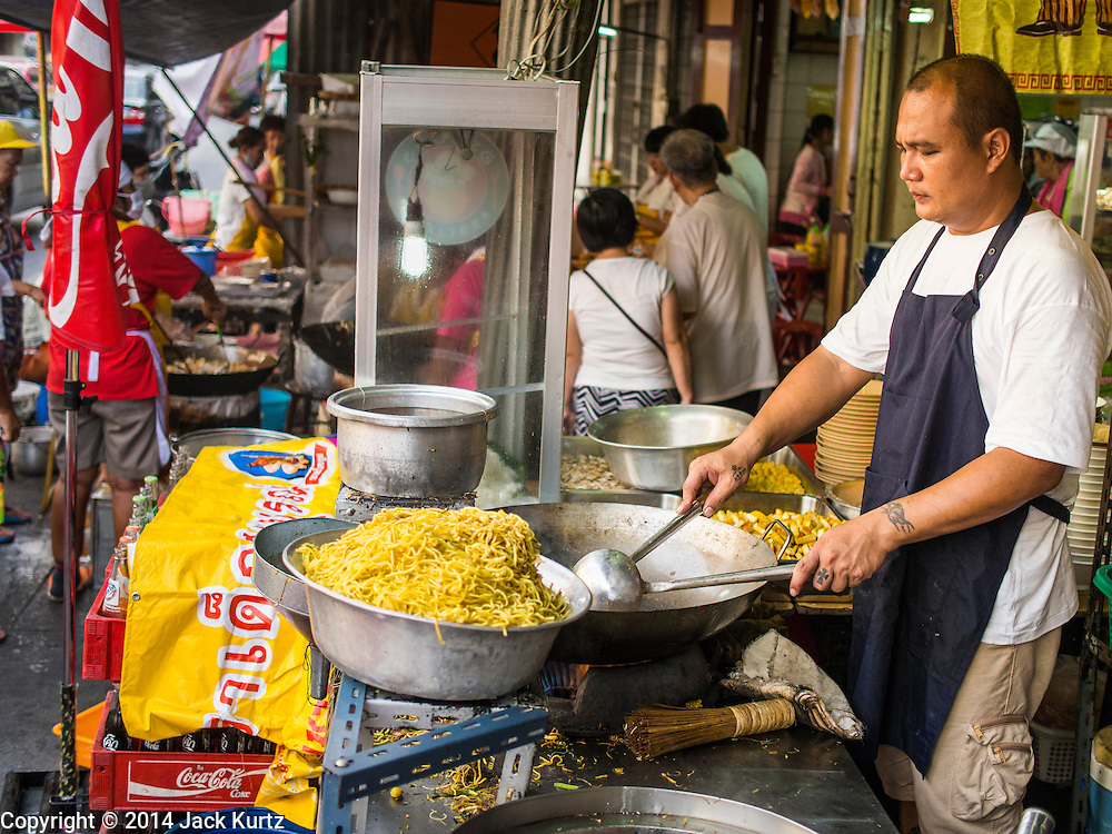 23 SEPTEMBER 2014 - BANGKOK, THAILAND: A vendor stir fries meatless noodles on the first day of the Vegetarian Festival near the Chit Sia Ma Chinese shrine in Bangkok. The Vegetarian Festival is celebrated throughout Thailand. It is the Thai version of the The Nine Emperor Gods Festival, a nine-day Taoist celebration beginning on the eve of 9th lunar month of the Chinese calendar. During a period of nine days, those who are participating in the festival dress all in white and abstain from eating meat, poultry, seafood, and dairy products. Vendors and proprietors of restaurants indicate that vegetarian food is for sale by putting a yellow flag out with Thai characters for meatless written on it in red.    PHOTO BY JACK KURTZ