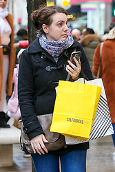 © Licensed to London News Pictures. 23/12/2018. London, UK. A woman with shopping bags on the mobile phone. Last minute Christmas shoppers take advantage of pre-Christmas bargains in London's Oxford Street. Fewer shoppers have been reported shopping in Britain's high streets as online sales increase. Photo credit: Dinendra Haria/LNP