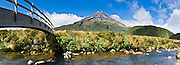 "A footbridge arches across a stream near Mount Egmont or Taranaki (2518 meters / 8261 feet) in Mount Egmont National Park, New Zealand, North Island. Featured as a stand-in for Mount Fuji in the Tom Cruise motion picture, ""The Last Samurai"". Panorama stitched from 4 overlapping photos."