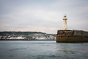 Dover Breakwater Lighthouse at the end of Dover Harbour, in the background ferries can be seen in the port of Dover and the White Cliffs of Dover as seen in a boat in the Dover Strait, Dover, Kent, England, United Kingdom. The lighthouse is white, but covered in orange from where it has been weathered by sea water and rust. (photo by Andrew Aitchison / In pictures via Getty Images)