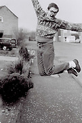 Masked man jumping in the air, Essex, UK, 1985
