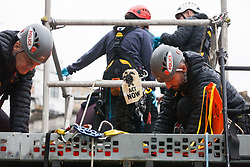 London, UK. 7 October, 2019. A climate activist from Extinction Rebellion holds up a banner reading 'Act Now' as a specialist team of Metropolitan Police officers works to remove him from a scaffold tower used to block Trafalgar Square on the first day of International Rebellion protests to demand a government declaration of a climate and ecological emergency, a commitment to halting biodiversity loss and net zero carbon emissions by 2025 and for the government to create and be led by the decisions of a Citizens' Assembly on climate and ecological justice.