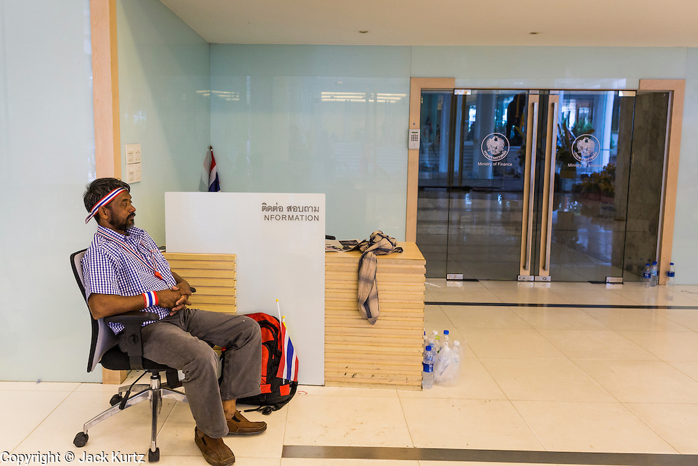 26 NOVEMBER 2013 - BANGKOK, THAILAND:  A Thai anti-government protestor relaxes in the lobby of the Ministry of FInance.  Protestors opposed to the government of Thai Prime Minister Yingluck Shinawatra spread out through Bangkok this week. Protestors have taken over the Ministry of Finance, Ministry of Sports and Tourism, Ministry of the Interior and other smaller ministries. The protestors are demanding the Prime Minister resign, the Prime Minister said she will not step down. This is the worst political turmoil in Thailand since 2010 when 90 civilians were killed in an army crackdown against Red Shirt protestors. The Pheu Thai party, supported by the Red Shirts, won the 2011 election and now govern. The protestors demanding the Prime Minister step down are related to the Yellow Shirt protestors that closed airports in Thailand in 2008.    PHOTO BY JACK KURTZ