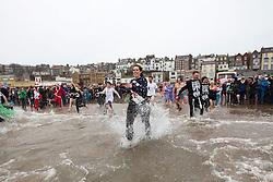 © Licensed to London News Pictures. 01/01/2016. Scarborough UK. Daring dippers took to the North Sea in Scarborough once again on the first day of the year for the Annual New Year's day dip.Photo credit: Andrew McCaren/LNP