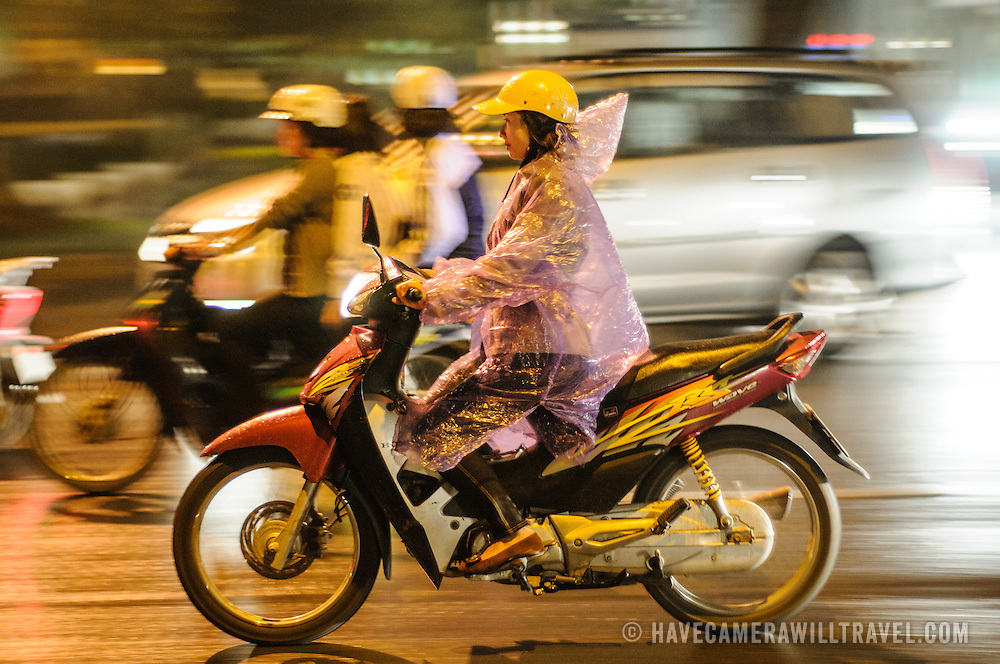 A woman on a motorbike negotiates hectic traffic of Hanoi's Old Quarter at night in the rain.