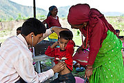 Dr Gyanendra Sunar working at the Child Welfare Scheme Nepal (CWSN) mobile health clinic in Gagan Gauda, Kaski District, Pokhara, Nepal. The clinic runs every Friday in this remote district.