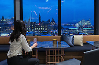 woman enjoying a drink and the view of Ottawa Skyline at dusk from the lounge at the top of Andaz Hotel, 325 Dalhousie, Ottawa