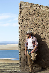 portrait of a very good looking cowboy in New Mexico against an adobe wall