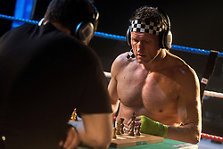 © Licensed to London News Pictures. 24/03/2013. London, UK. Tim Woolgar (L) and Andy Costello compete in a bout of Chessboxing Grand Prix in Scala, London, Saturday evening 23 March 2013. The hybrid sport combines chess with boxing in alternating rounds. The winner is decided by a knock out or checkmate, whichever comes first. A full match consists of eleven rounds: six rounds of chess, each four minutes long, and five rounds of boxing, each three minutes long (four minutes under amateur rules).[4] The match begins with a chess round which is followed by a boxing round. Rounds of chess and boxing alternate until the end of the match.[1][5] There is a one-minute break between each round, during which competitors cool out and change gear.. Photo credit : Peter Kollanyi/LNP