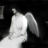 A young seated woman with angel wings