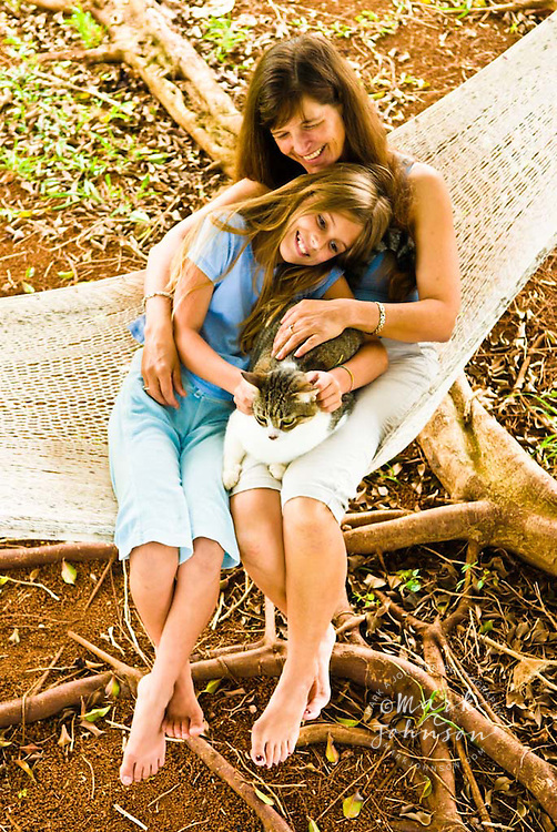 Mother & daughter & pet cat in hammock together