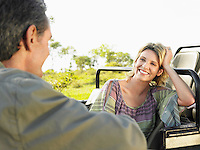 Man and woman talking woman leaning with elbow on jeep focus on woman