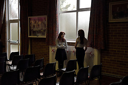 """© London News Pictures. """"Looking for Nigel"""". A body of work by photographer Mary Turner, studying UKIP leader Nigel Farage and his followers throughout the 2015 election campaign. PICTURE SHOWS - Young Independence member Rhiannon Ellis talks to her sister Jessica as she fiddles with England flags decorating Cliffsend Village Hall, nr Ramsgate in Kent, before a public meeting on March 31st 2015. Rhiannon, a dedicated member of UKIP's youth wing 'Young Independence' travelled from her home in the Midlands to Nigel Farage in his bid to win the South Thanet seat. . Photo credit: Mary Turner/LNP **PLEASE CALL TO ARRANGE FEE** **More images available on request**"""