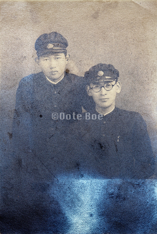 silver mirroring on a vintage portrait of two young adult boys wearing a school uniform Japan