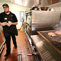 Sadler Spencer, an employee with Malco, walks in the kitchen area holding bags of french fries as two hamburgers cook on the grill on Thursday afternoon. The theater chain has upgraded its menu to include, burgers and fries, chicken tenders along with other food items.