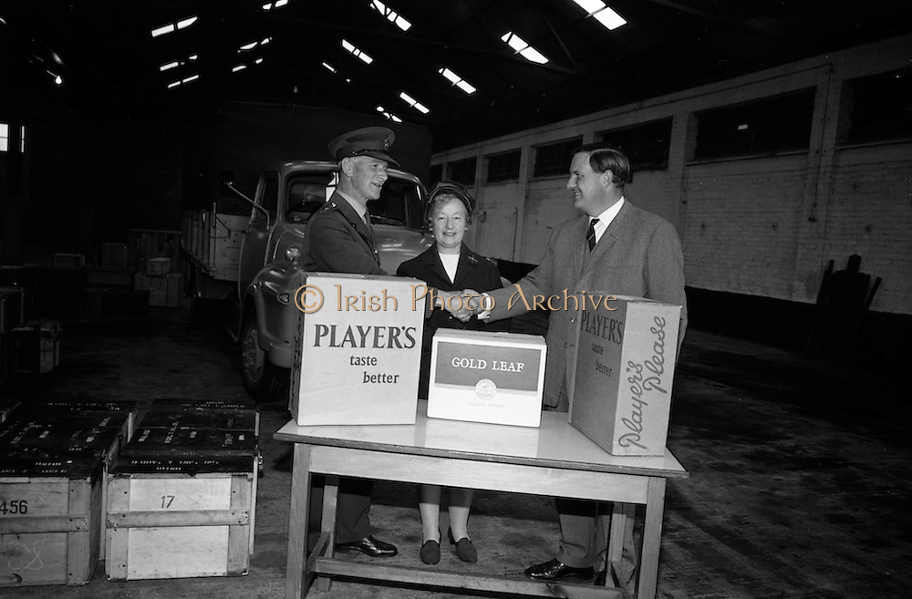 10/10/1966<br /> 10/10/1966<br /> 10 October 1966<br /> Cigarettes for Cyprus Troops. Mr. John Fry, Marketing Manager Player and Wills Ireland Ltd. hands over a gift of fifty thousand specially packed cigarettes to Lt. Col. James Moylett, Manager, Army Canteen Board at McKee Barracks, Dublin. The cigarettes were for the 7th Infantry Group on peacekeeping duty in Cyprus. <br /> Centre is Miss M.B. Murphy, Honorary Secretary of the Irish Red Cross Committee for comforts for Troops serving overseas.