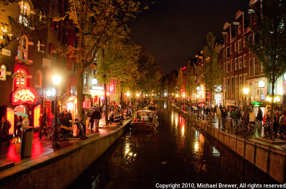 Amsterdam, Holland. The red light district at night.  Lights shimmer off the water of the canal.