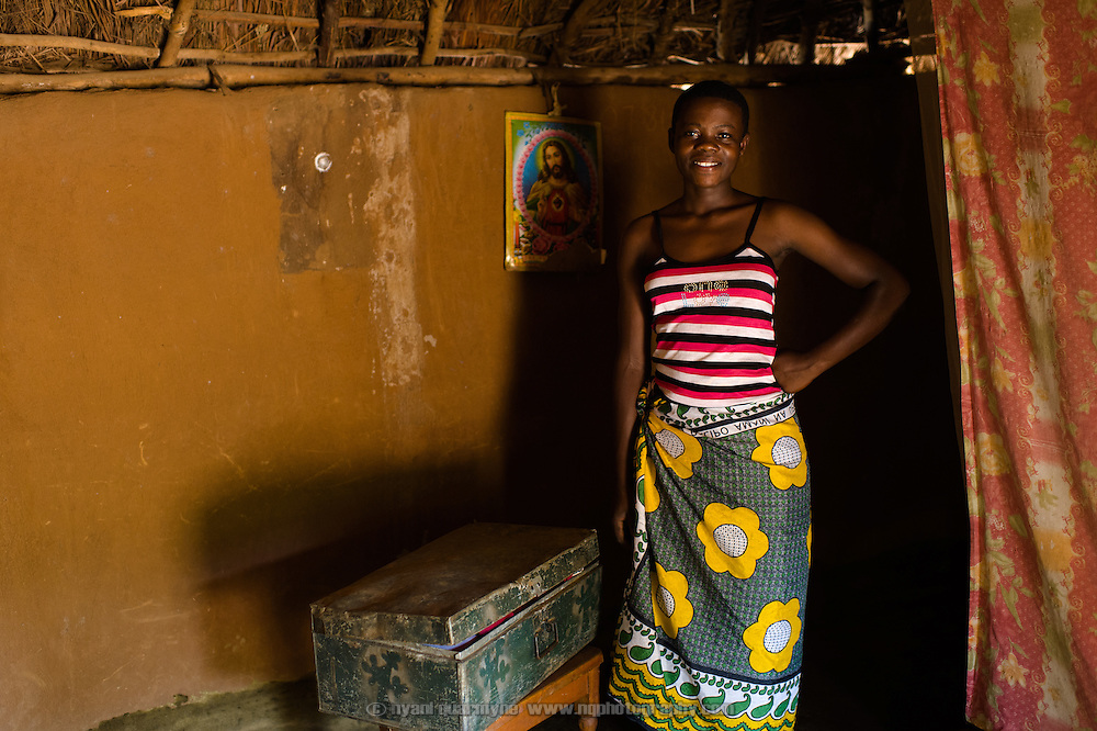"Catherine Apoyo, pictured on 2 August 2014, keeps her Afripads in a metal trunk of her belongings at her home near Tororo, Uganda. She says, has been using Afripads for three months, and says of them ""It's very good. It's comfortable."" Previously she would use rags when she had her period, and said, ""Sometimes blood would come out onto my skirt, or they can even fall down when you are walking."" She would stay home from school at times, because she was not comfortable going out with the rags."