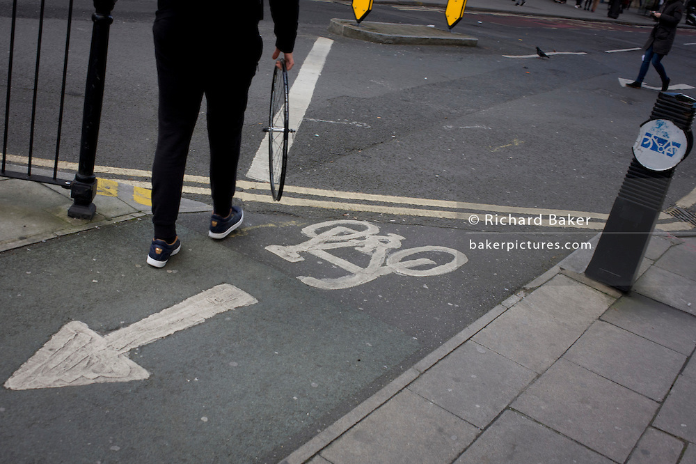 A person carries a bicycle wheel, minus its tyre, past a cycle path in central London.