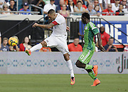 JACKSONVILLE, FL - JUNE 07:  Forward Clint Dempsey #8 of the United States shoots in front of defender Juwon Oshaniwa #13 of Nigeria during the international friendly match at EverBank Field on June 7, 2014 in Jacksonville, Florida.  (Photo by Mike Zarrilli/Getty Images)
