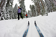 Low angle view of cross country ski tips and two young women nordic skiing on a cross country trail in the snow in Bend, Oregon. (releasecode: jk_mr1033, jk_mr1032) (Model Released)