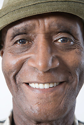 Portrait of an older man wearing a hat smiling,