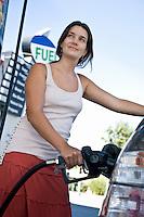 Smiling woman refueling car at natural gas station