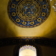 Light shines through a grilled window onto a design on the ceiling in Hagia Sophia. Originally built as a Christian cathedral, then converted to a Muslim mosque in the 15th century, and now a museum (since 1935), the Hagia Sophia is one of the oldest and grandest buildings in Istanbul. For a thousand years, it was the largest cathedral in the world and is regarded as the crowning achievement of Byzantine architecture.