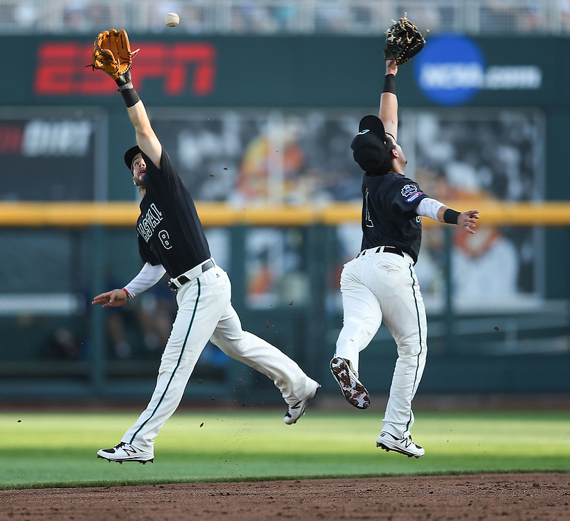 OMAHA, NEB.  -- 06/19/2016:   Coastal Carolina's Tyler Chadwick (8), left, and Michael Paez (1) reach for a ball hit by Florida's Dalton Guthrie (5) in the bottom of the first inning during game four of the College World Series at TD Ameritrade Park in Omaha, Neb., Sunday, June 19, 2016.<br /> MATT DIXON/THE WORLD-HERALD